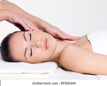 Massage for the face and neck of young beautiful woman in spa salon - close-up portrait