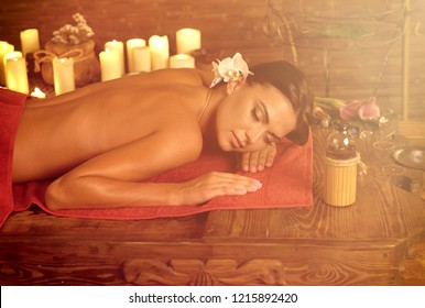 Massage Filipino of woman in spa salon. Girl candles in massage spa salon. Sun flare luxary interior in oriental therapy. Dry flowers in clay vases. Color tone on shiny sunlight background.