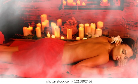 Massage Filipino of woman in spa salon. Girl on candles aglow background in steam room. Luxary ayurveda interior in oriental therapy salon. Photo effect with red toning. Artistic effect of steam