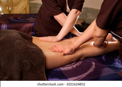 Massage in four hands in the spa salon.