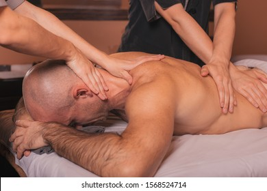 Massage in four hands in the spa salon.Spa man. Male enjoying relaxing back massage in cosmetology spa centre. Body care, skin care, wellness, wellbeing, beauty treatment concept.