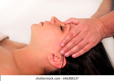 Massage of head and face in spa center. Massage wellness studio. Happy young woman enjoying face and collar area massage getting spa treatment in salon. Facial energy massage. Body and health care.