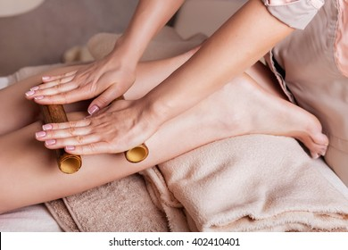 Massage of human foot in spa salon  with bamboo sticks. Closeup of feet,