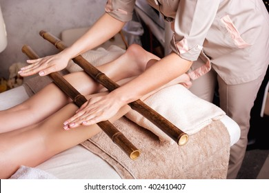 Massage of human foot in spa salon  with bamboo sticks. Closeup of legs