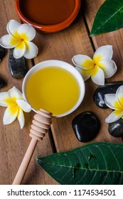 Massage oil,  with honey wood spoon, plumeria flowers and leaves,  black round stones and wooden background