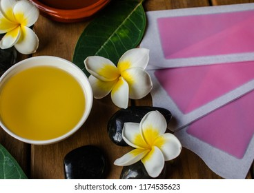 Massage oil,  with pink cold wax strips, plumeria flowers and leaves,  black round stones and wooden background