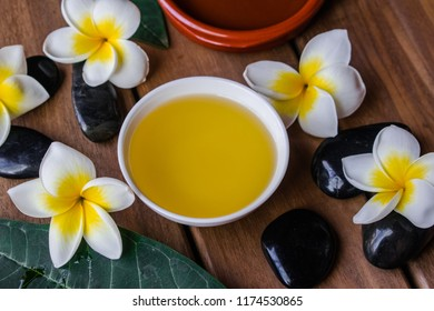 Massage oil with plumeria flowers and leaves, black round stones and wooden background