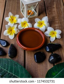 Massage oil with plumeria flowers and leaves, orange candle,  black round stones and wooden background