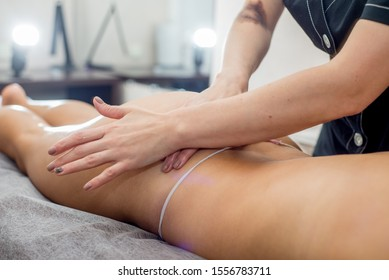 massage on the buttocks and legs. Masseuse hands massage the buttocks and legs of women on a massage table in a spa salon