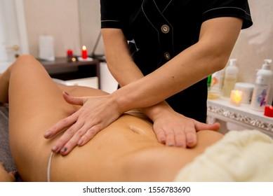massage on the stomach. Masseuse hands massage woman in spa salon