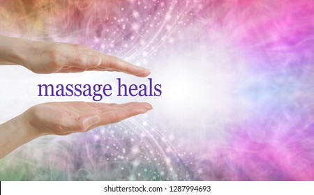 Massage REALLY DOES heal so give it a try - parallel hands with the words MASSAGE HEALS floating between against a beautiful pink blue glittery sparkling background and copy space