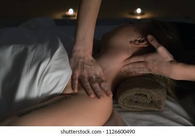 a massage in the massage room, relaxation and care, the patient's body and the hands of the masseur, body oil