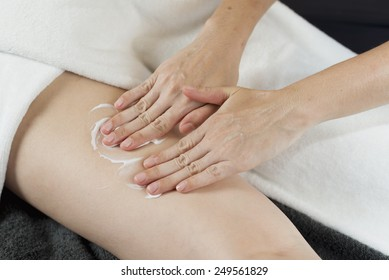 Massage series : Therapist applying cream on woman's leg