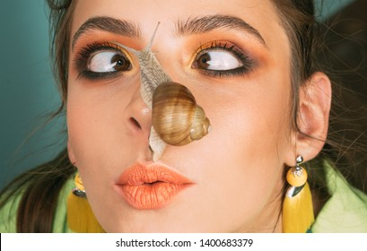 Massage with snail. Skincare repairing. Healing mucus. Having fun with adorable snail. Cosmetics and snail mucus. Cosmetology beauty procedure. Girl fashionable makeup face and cute snail. Skin care.