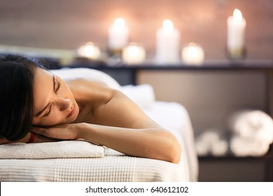 Massage and spa concept. Beautiful girl in spa salon on candle background. Young woman in modern massage parlor