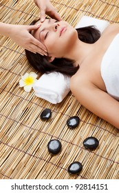 massage in spa salon, woman laying on bamboo mat