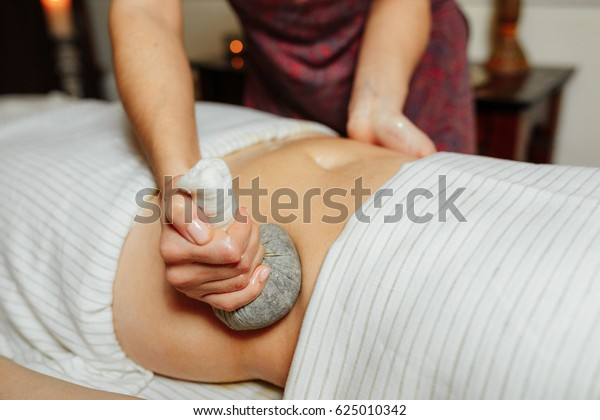 Massage of the stomach with herbal compresses