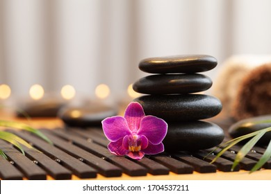 Massage stone, orchid flowers and burning candles. Spa and beauty background.