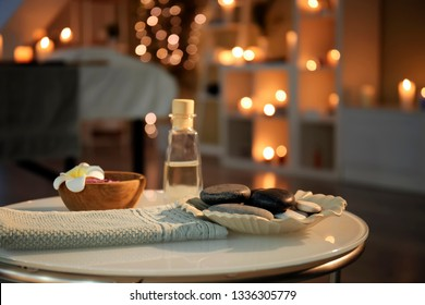 Massage stones, towel and essential oil on table in spa salon