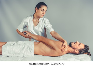 Massage stretching therapy. A young professional female masseur makes Thai massage. Patient is lying down on a bed and is covered with white towel. Treatment, rest, relaxation, spa. Studio shot