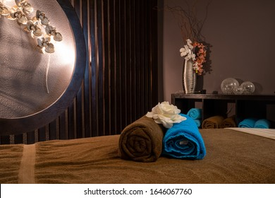 Massage table with colorful towels on a wooden background with faint lights to relax