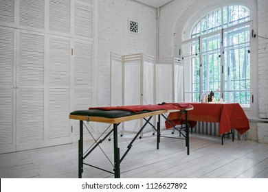 Massage table in a light room with a big window. Horizontal shot