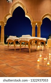 Massage tables set up on a candlelit patio at a resort.