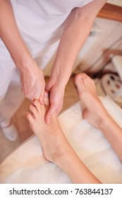 the massage therapist does a foot massage to a pretty young girl