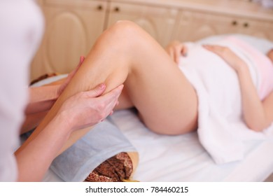 massage therapist doing a foot massage for a pregnant woman on a spa salon background