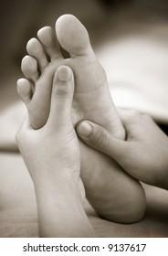 A massage therapist doing reflexology foot massage on a patient's foot