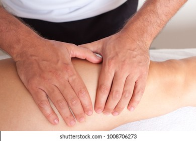Massage therapist giving a leg massage