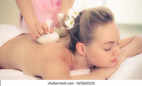 Massage therapist holds a herbal compress to do treatment to woman lying on spa bed in a luxury spa resort. Wellness, stress relief and rejuvenation concept.