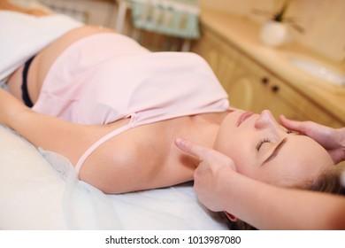 massage therapist makes a beautiful pregnant girl face massage
