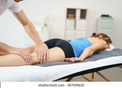 Massage Therapist Massaging the Legs of a Woman Lying Prone on the Bed.