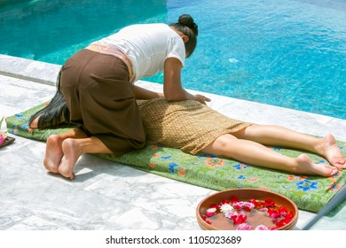 Massage therapist is Thai massage to beautiful customers by the pool. and the foot bath on the side.