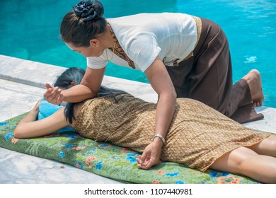 Massage therapist is Thai massage to beautiful customers by the pool. and the foot bath on the side.Koh Samui Thailand