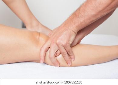 Massage therapist treating a knee pain
