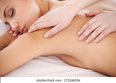 Massage for tired body. Beautiful young woman lying on front and keeping eyes closed while massage therapist massaging her back