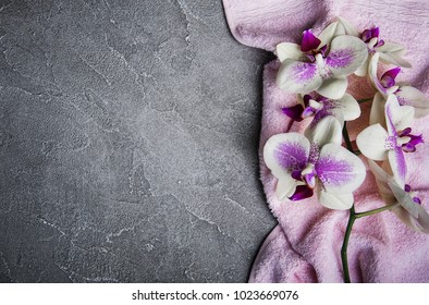 Massage towel and orchids flowers on a gray stone background
