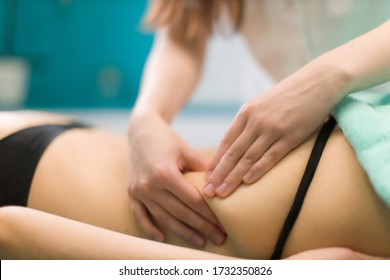 A massage of a white woman lying in a wellness salon