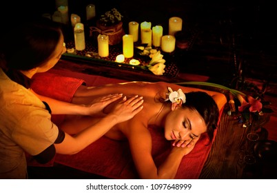Massage of woman in spa salon. Girl on candles background treats problem nack and sholders. Luxary interior with working hands masseuse. Crop of bare back has relax. Alternative medicine on very dark