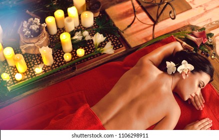 Massage of woman in spa salon. Girl on candles background in massage spa salon. Luxary interior in oriental therapy salon. Female have relax after sport. Top view and rays falling from above.