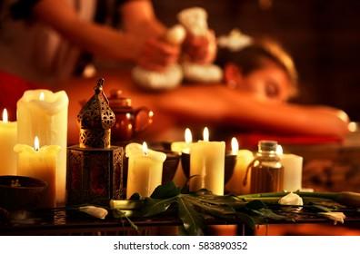 Massage der Frau im Spa-Salon. Mädchen im Massagesalon. Luxuriöses Interieur im orientalischen Therapiesalon. Nahaufnahme von weiblichen Massage Hände geben Kräutern heiße Ball Therapie. Kerzen im Vordergrund brennen.