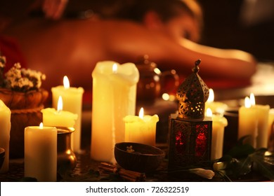Massage of woman in spa salon. Girl on candles background treats problem back. Luxary interior with working masseuse. Shirodhara Pot background. Candles in foreground. Alternative medicine.