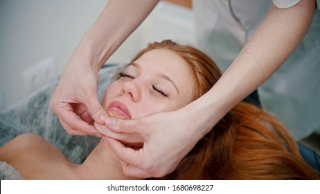 Massage - woman massage therapist massaging the face of a red-haired woman