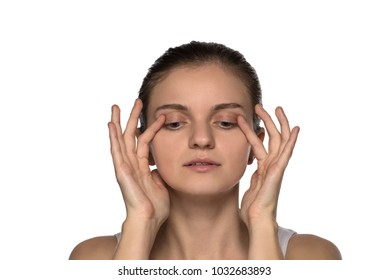 Massage, yoga, gymnastics or rejuvenating exercises for the muscle of the face makes the girl own hands on a white background