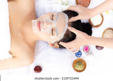 Massager is massaging her beautiful customer head. Attractive beautiful woman feels relaxing and happiness. Charming beautiful girl use collagen mask for nourishing her face skin with herbs background