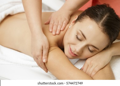 Massaging the stress away. Attractive young woman smiling enjoying full body massage at the spa resort clinic beauty salon body skincare masseur happiness relaxation relaxing pampering concept
