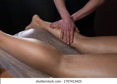 Massagist scrubbing woman booty and legs natural scrub in spa salon. Procedure of peeling body for young girl in cosmetology clinic, closeup. Hands massaging client legs. Skincare bodycare concept.