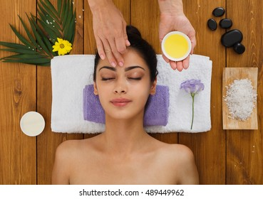 Massagist with woman patient in aroma spa wellness center. Professional face lifting lemon massage to beautiful girl in cosmetology cabinet or beauty parlor.